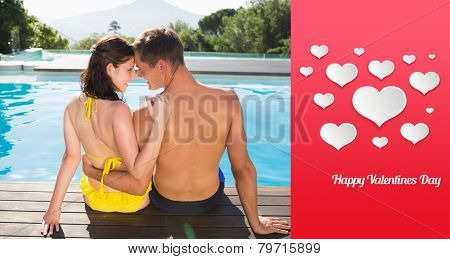 Couple sitting by swimming pool on a sunny day against happy valentines day