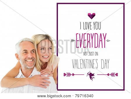 Happy man giving his partner a piggy back against valentines day greeting