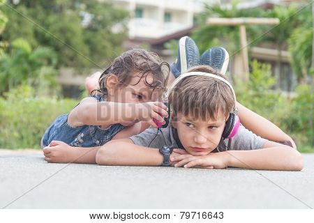 Cute child boy listening to music with headphones outside