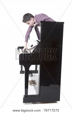 Teenage Boy And Upright Black Piano In Studio