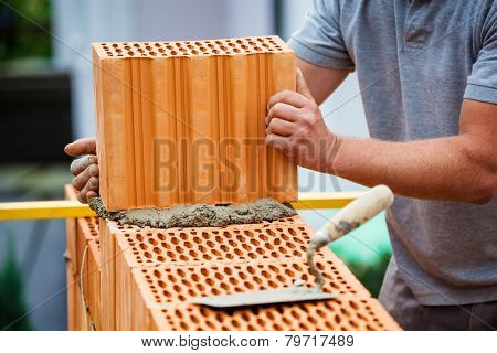 anonymous construction worker on a construction site in home building erected a wall of bricks. solid brick wall of a house. icon image for undeclared work and botch