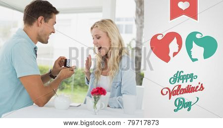 Man proposing marriage to his shocked blonde girlfriend against cute valentines message