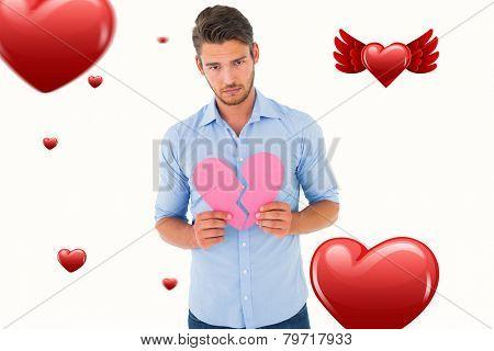 Sad man holding a broken heart against hearts