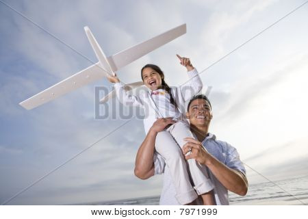 Hispanic Dad Playing Holding Girl High On Shoulder