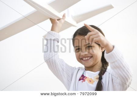Smiling Hispanic Girl Playing With Toy Model Plane