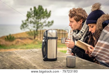 Young couple under blanket reading book outdoors in a cold day