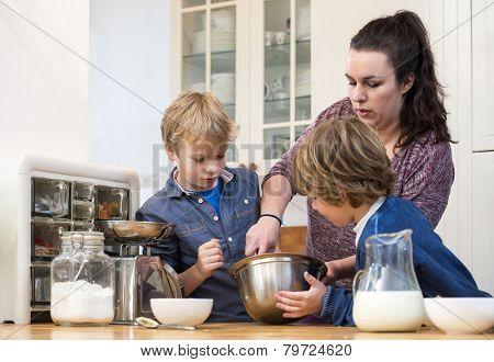 Boys looking  closely at a woman, giving a baking workshop, showing them how to whisk cupcake batter in a kitchen