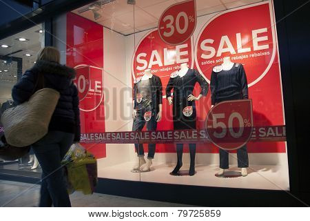Woman Passing Sale In Shopping Wndow Of Fashion Store
