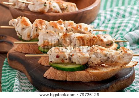 Chicken kebabs on skewers with toast