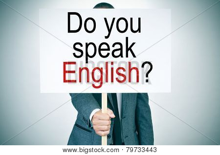 a man in suit showing a signboard with the sentence do you speak english? written in it