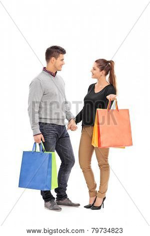Full length portrait of a young couple with shopping bags having a conversation isolated on white background