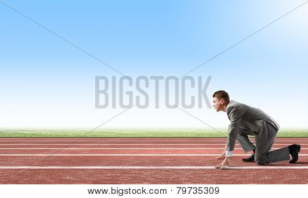 Side view of young businessman in start position on track