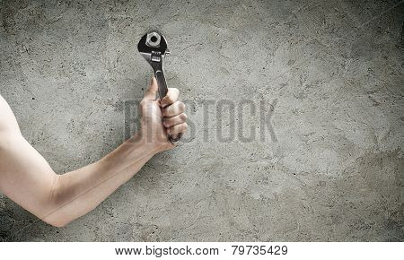 Close up of hand spinning nut with wrench