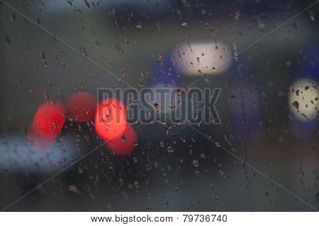 Red Lights Seen Through Wet Windshield During Rainfall
