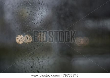 Traffic Lights Seen Through Wet Windshield During Rainfall