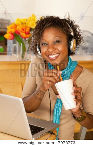 Young Woman Drinking Beverage And Using Laptop