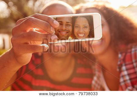 Couple On Holiday Taking Selfie With Mobile Phone