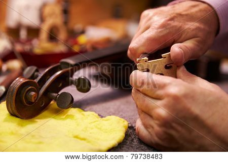 Close Up Of Man Restoring Violin In Workshop