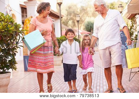 Grandparents With Grandchildren Carrying Shopping Bags