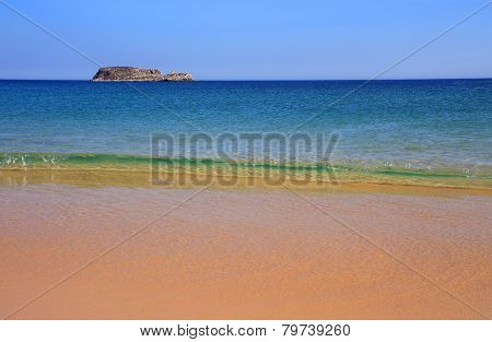 Turquoise sea and deserted Algarve beach.