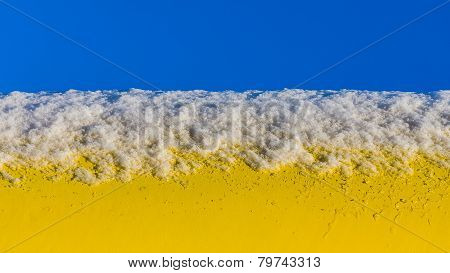 Snow on a yellow pipe