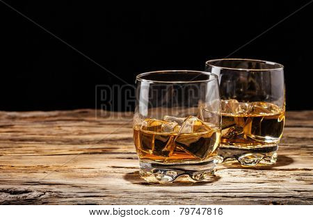 Whiskey drinks on wooden table with black background