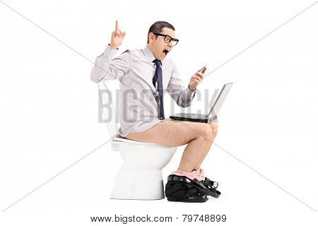 Angry businessman yelling at his phone seated on a toilet isolated on white background