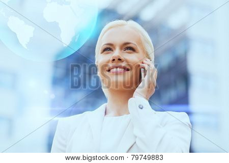 business, technology and people concept - smiling businesswoman with smartphone and globe hologram talking over office building