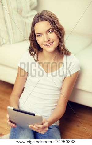 home, technology and internet concept - smiling teenage girl sitting ong the floor with tablet pc computer at home