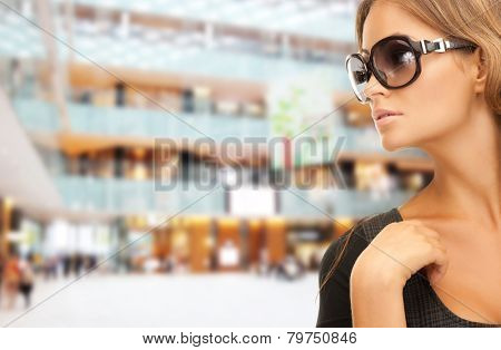 people, fashion, shopping, eyewear and style concept - beautiful woman in shades over mall background