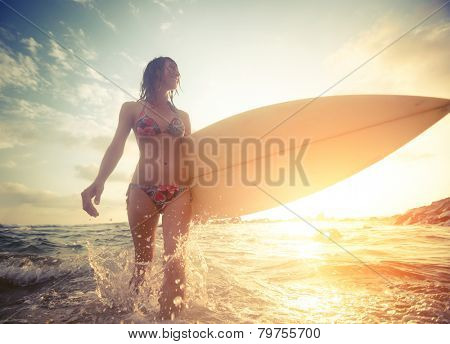 Surfer girl walking with board on the shallow water with water splashes