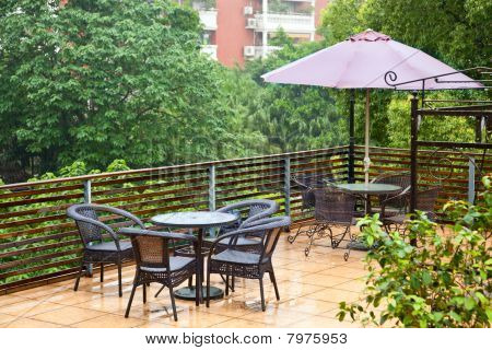 Patio Rattan Chairs And Table  In Raining