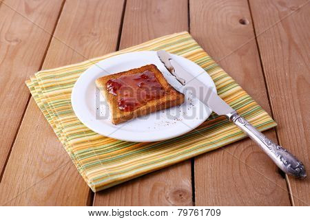 Toast bread spread with jam on plate and napkin with knife on wooden table background