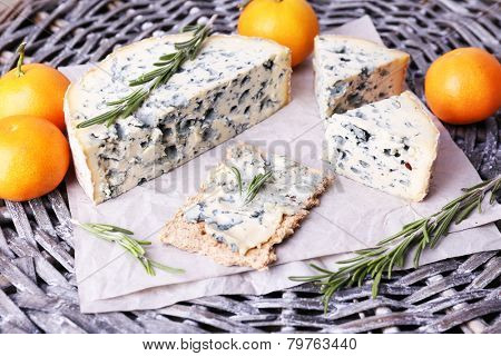 Blue cheese with sprigs of rosemary and oranges on wicker mat background
