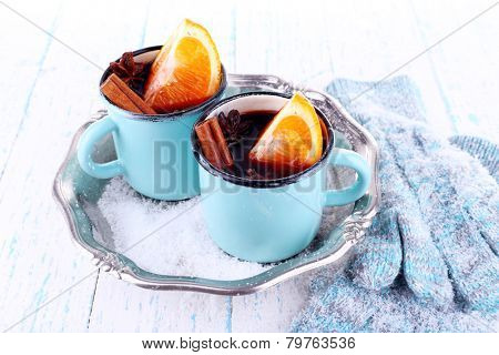 Mugs of mulled wine, piece of orange and spice on metal tray with mittens on color wooden table background
