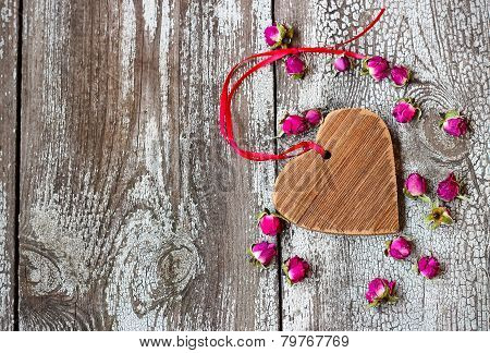 Wooden Heart With Red Ribbon And Small Dried Rosebuds On A Wooden Table