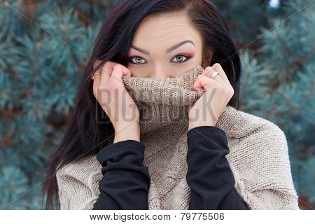 beautiful happy young woman was wearing a high neck sweater, in the forest in winter