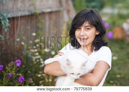 Cute teengirl with a cat outdoors.