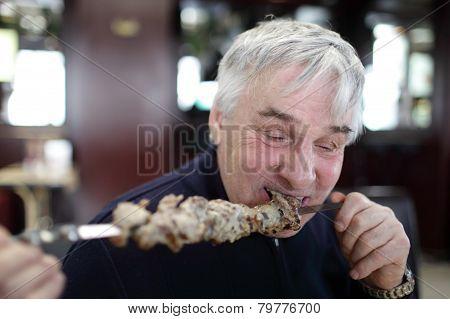 Senior Man Eating Kebab On A Stick