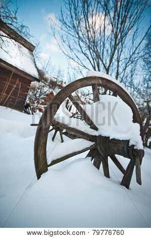 Old wooden cottage and wooden Romanian wheel covered by snow. Cold winter day at countryside