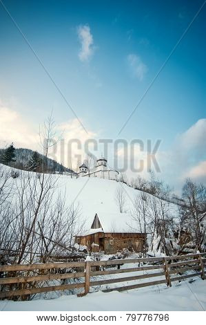 View of Romanian small church on hill covered with snow. Winter landscape with orthodox church