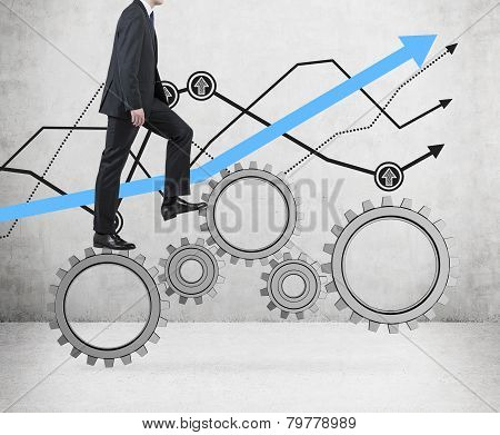 Businessman Walking On Cogs