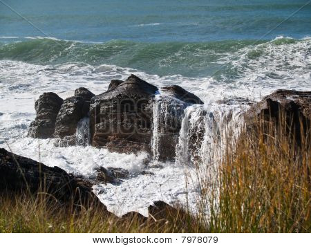Ocean waves roll over rocks.