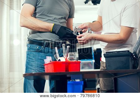 Two man in the workshop, using a micrometer