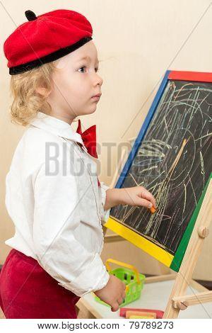 Cute Child Girl Drawing Chalk On Easel In Suit Of Artist In Preschool In Kindergarten