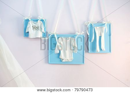 Blue baby clothes on the clothesline ribbons on the wall