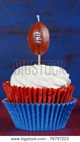 Super Bowl Party Cupcake With Football Candle In Red, White And Blue Colors.