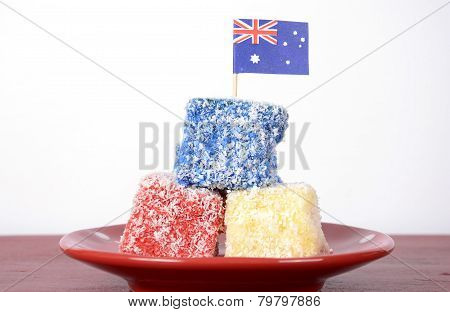 Happy Australia Day Red, White And Blue Lamingtons Party Food On Red Wood Table Against White Backgr