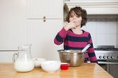 picture of finger-licking  - Portrait of young girl licking batter while preparing cupcake in kitchen - JPG