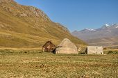 stock photo of yurt  - Yurts of nomads on green grasslands in Kyrgyzstan - JPG